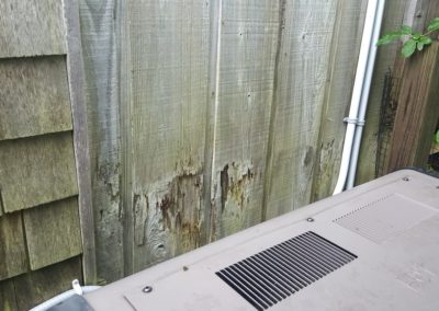 Damage to wood siding under outdooor shower, accelerated due to frequent exposure to water.