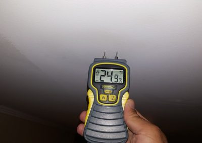 Home Inspector Using a Moisture Meter For Checking Stain Of a Celling While Home Inspection Services Executed In a House