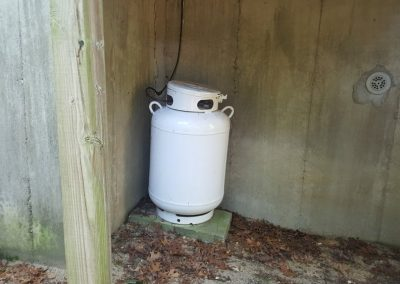 Home Inspection Services Of a House Where Propen Gas Tank Is Being Leaned On Because Of Soil Erosion